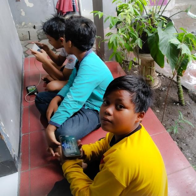 Anak-anak perumahan yang lesehan di teras depan rumah untuk akses free wifi.